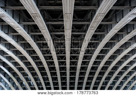 Detail of riveted steel beams supporting span of bridge crossing the River Thames