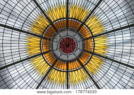 Detail of stained glass ceiling with solar centre and rays emanating in hub and spoke pattern