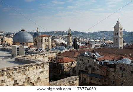 JERUSALEM ISRAEL - MARCH 25 2017: View from above of the old city of Jerusalem. On the right are the gray domes of the Holy Sepulcher Church on the left is the bell tower of Rudimer
