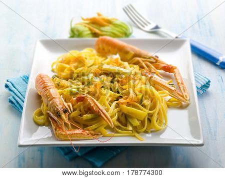 pasta with norway lobster zucchinis flower and saffron, selective focus