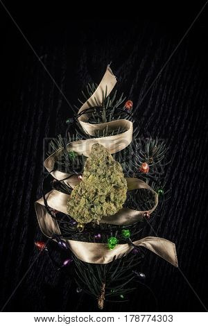 Cannabis dry bud over pine tree branch with christmas lights and ribbon resembling a tree over black background