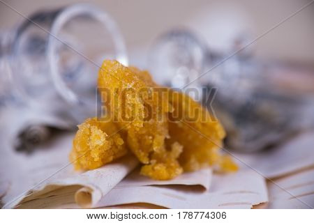 Detail of marijuana extraction concentrate aka wax crumble on wood background with glass rig