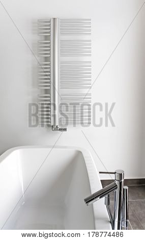 Contemporary light bathroom in detail, modern bathroom with bath, design bathroom heating