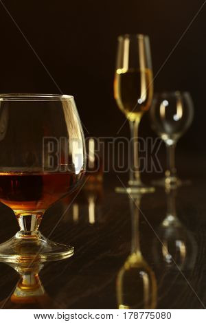 Two glasses of brandy or cognac and bottle on black background.