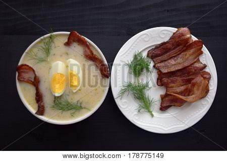 soup with  dill, egg and bacon  on a black background.