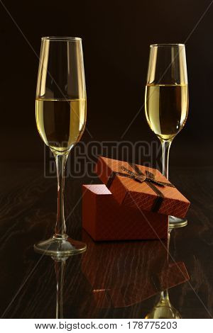 Two glasses with white wine and gift box on mirror table. Celebrities composition. Your text here
