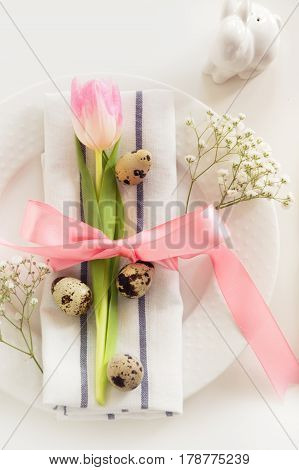 Elegance table setting with pink ribbon and tulip on white background. Easter romantic dinner. Top view.
