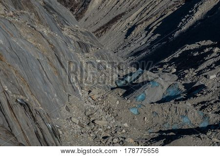 Glacier with ice blocks partly covered by rocks pebbles and dirt in a ravine at the end of Mer de Glace in Chamonix France