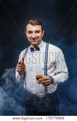 Portrait of a handsome smiling man in bow-tie and suspenders holding glass of beverage and cigar while looking at camera. Smoke on background. Studio shot