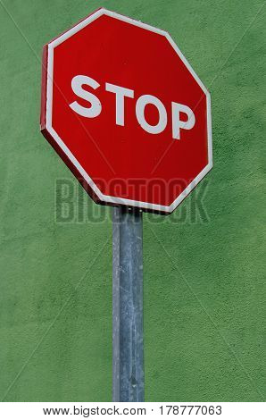Stop sign over a wall painted in green. Urban roadsign and signage