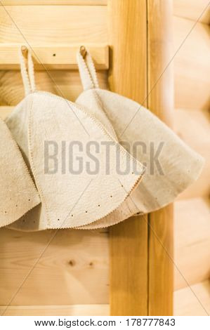 Three Russian White Wool Hats for Sauna Banya Bath House on a wooden background close up. Bath accessories in traditional Russian sauna. concept rest.