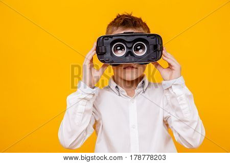 Small boy in white shirt looking at camera through virtual reality headset isolated on orange background.