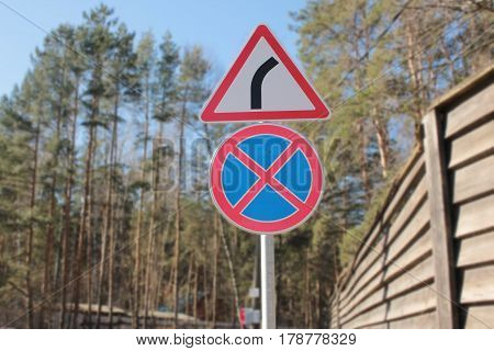 Traffic signs give way and you can't stop in a forest and fences