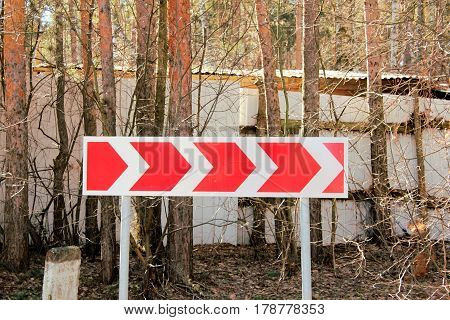 Direction road sign dangerous bend on a background of trees