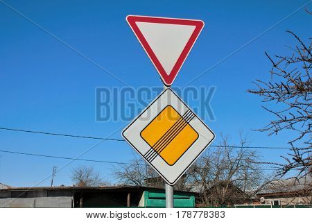 Signs give way and the end of the main road on blue sky background
