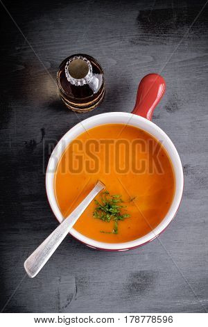 Pumpkin creme soup with a spoon served on a table