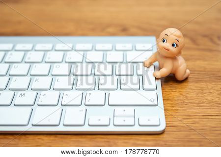 Comic photo - little baby doll is trying to climb on the keyboard, lying on a wooden table