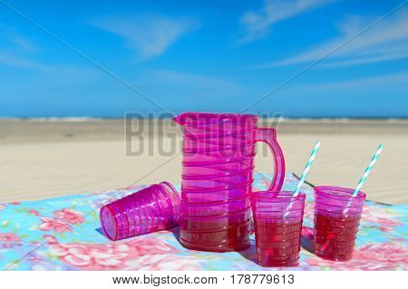 Pink jar and glasses with lemonade at the beach
