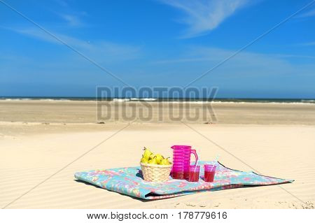 Basket fresh pears and jar with lemonade at the beach