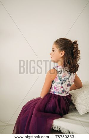 Beautiful girl in a purple dress and flower blouse posing for a photographer. Photosession for the magazine.