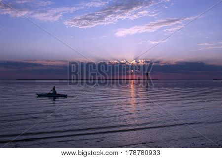 Silhouette of a kayaker in the channel waters around Jekyll Island, Georgia at sunset