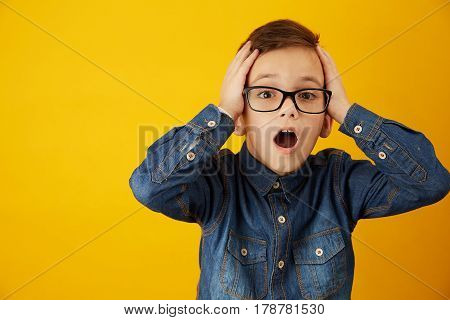 Portrait of a boy wearing spectacles with a shocked facial expression