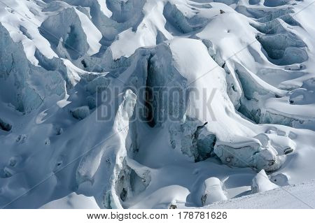 Close-up of Glacier d'Argentiere with snow covered crevasses and seracs formed while flowing down the valley in winter.