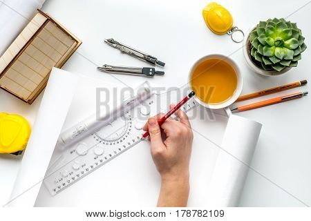 Architects workplace with constructor tools with miniature and hands on white table background top view