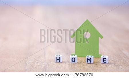 HOME horizontal word of cube letters behind green house symbol on wooden surface.