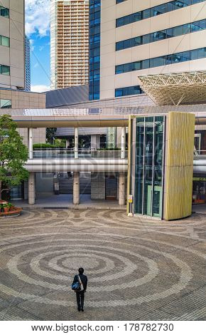 Unknown Man Walking Through Circular Courtyard Of The Typical Living Building In Tokyo, Japan