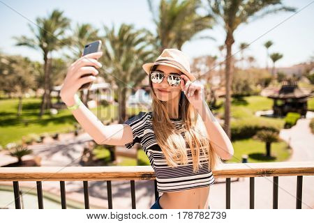 Cheerful Young Woman In Hat And Sunglasses Taking Selfie With Mobile Phone On Summer Resort Palms Ba