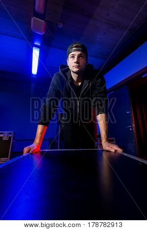 Roadie rolling a flightcase back stage in dim, blue light druing a concert in a venue.