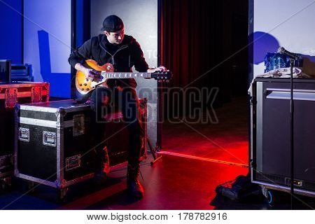 Roadie tuning a guitar for the guitarist next to the stage entrance, sitting on a flight case