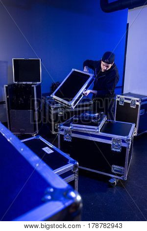 Roadie unpacking a mixing table for a dj on a flightcase, in preparation for an event in a concert hall