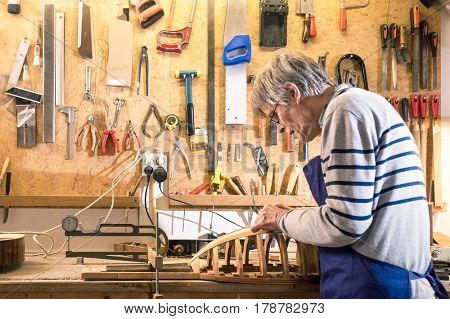Luthier working at his lute on the workbench with his tools on the background