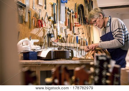 Luthier presicely carving the body of his halfway finished lute with guitar headstocks in the foreground