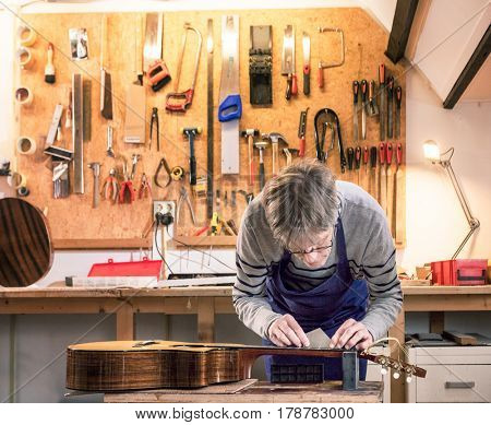 Luthier working on a workbench measuring and leveling the frets of a guitar with his tools in the background