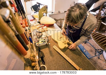 Guitar repairer clearing the sawdust from the neckpocket of an electric guitar