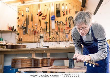 Luthier filing the frets of an acoustic guitar on the workbench poster