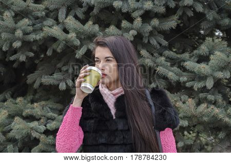 Beautiful girl with long hair in the background of a coniferous tree with a cardboard cup of a hot drink