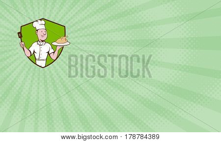 Business card showing Illustration of a chef cook serving roast chicken on a platter on one hand and holding a spatula on the other hand viewed from front set inside shield crest done in cartoon style.
