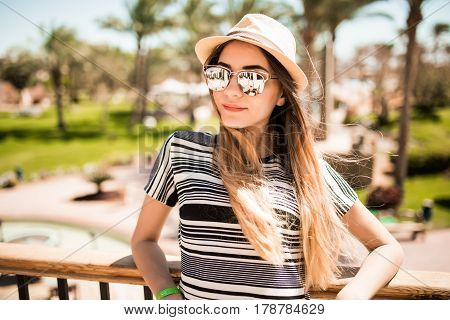 Portrait Of Relaxed Happy Smile Young Woman In Hat And Sunglasses On Terrace Of Hotel On Palms Backg