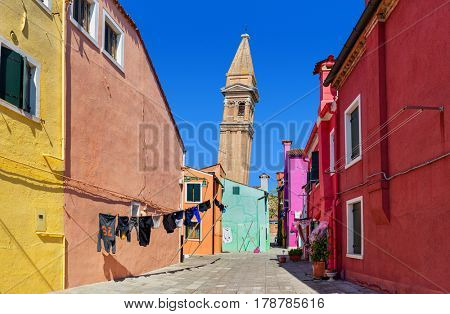 Small courtyard among colorful houses and leaning belfry on background under blue sky on Burano island, Italy.