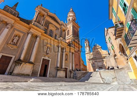 Small town square and Saint-Michel Archange Basilica under blue sky in Menton, France.