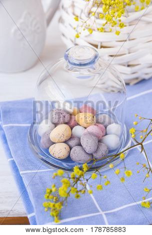 Colored speckled chocolate Easter eggs in crystal bell jar on blue napkin on white table basket with yellow flowers spring atmosphere