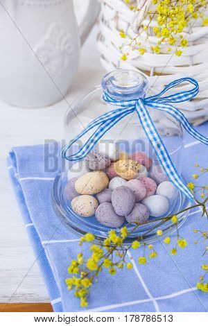 Colored speckled chocolate Easter eggs in crystal bell jar with ribbon on blue napkin on white table basket with yellow flowers spring atmosphere