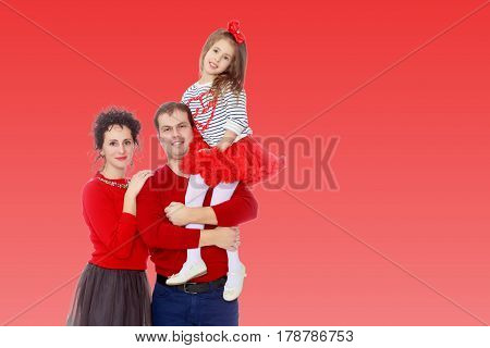 Happy young family dad mom and a little girl in bright red outfits . Dad holds daughter on hands.