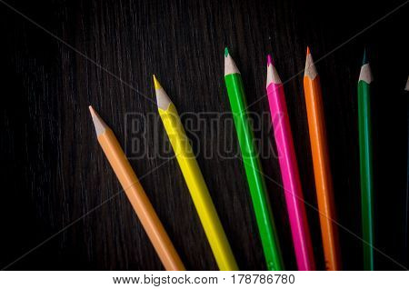 Set of colored pencils isolated on the wooden desk. Close up, right to left, space for text, top view