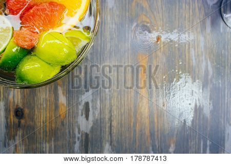 Citrus in water with bubbles in transparent plate Oranges, lemons, greyfrut, Pamela lemonade Space for signature on wood texture