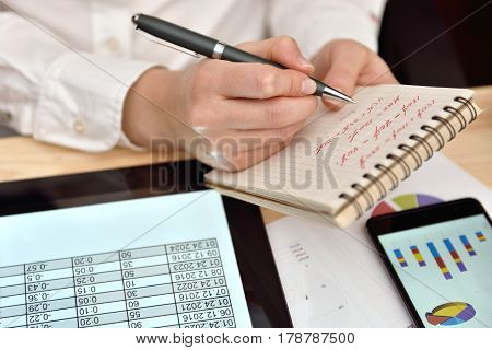 Woman Records Data In Notebook